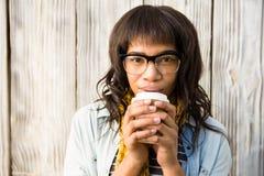 Τοποθέτηση γυναικών χαμόγελου περιστασιακή με τα γυαλιά πίνοντας τον καφέ Στοκ Εικόνες