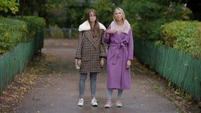 Τοποθέτηση δύο όμορφη γυναικών υπαίθρια το φθινόπωρο, που στέκεται ακόμα στα μοντέρνα ενδύματα φιλμ μικρού μήκους