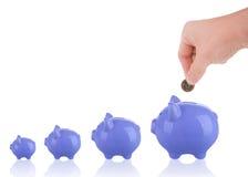 Τοποθέτηση ενός ευρο- νομίσματος στη piggy έννοια αποταμίευσης τραπεζών αυξανόμενη Στοκ Φωτογραφία