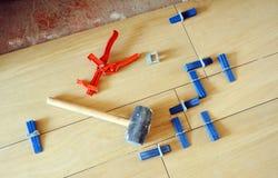 Τοποθέτηση ενός πατώματος κεραμιδιών κεραμικών πορσελάνης με τα ειδικά εργαλεία Στοκ Φωτογραφία