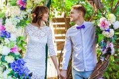 Τοποθέτηση ζευγών ευτυχίας σε μια αψίδα των λουλουδιών, που κρατά τα χέρια στοκ εικόνες με δικαίωμα ελεύθερης χρήσης