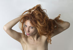 Τοποθέτηση και αρπαγές γυναικών η κόκκινη τρίχα της από τα χέρια Στοκ Εικόνες