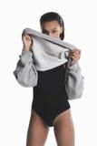 Τοποθέτηση κοριτσιών αφροαμερικάνων στο μαύρο κομπινεζόν και κρύβοντας πρόσωπο με το γκρίζο πουλόβερ Στοκ Εικόνες