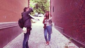 Τοποθέτηση κοριτσιών τουριστών για το καμεραμάν στη μικρή οδό φιλμ μικρού μήκους