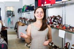 Τοποθέτηση νέων κοριτσιών καταστημάτων υποδημάτων με τα διαφορετικά παπούτσια στοκ εικόνες