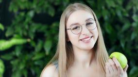 Τοποθέτηση νέων κοριτσιών χαμόγελου όμορφη με το φρέσκο μήλο eco φυσικό υπόβαθρο θερινών στο πράσινο δέντρων απόθεμα βίντεο