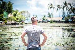 Τοποθέτηση νεαρών άνδρων στον τομέα λουλουδιών λωτού στη λίμνη, τροπικό νησί του Μπαλί, Ινδονησία Στοκ Εικόνες