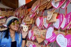 Τοποθέτηση ταξιδιωτικών ταϊλανδική γυναικών για τη φωτογραφία πυροβολισμού με την ξύλινη ετικέττα της Ema Στοκ Φωτογραφίες