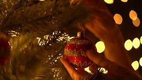 Τοποθέτηση της διακόσμησης στο χριστουγεννιάτικο δέντρο με τα φω'τα bokeh φιλμ μικρού μήκους