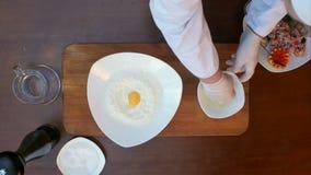 Τοποθέτηση του λέκιθου αυγών στο αλεύρι στο πιάτο απόθεμα βίντεο