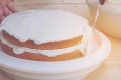 Τοποθέτηση του βουτύρου κέικ κρέμας με το χέρι που χρησιμοποιεί spatula Στοκ εικόνες με δικαίωμα ελεύθερης χρήσης