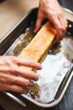 Τοποθέτηση του κέικ στο καυτό σιρόπι ζάχαρης Στοκ Εικόνες