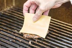 Τοποθέτηση του τυριού σε ένα ψημένο στη σχάρα χάμπουργκερ Στοκ φωτογραφία με δικαίωμα ελεύθερης χρήσης