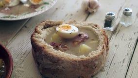 Τοποθέτηση των αυγών πάνω από την παραδοσιακή σούπα στο κύπελλο ψωμιού απόθεμα βίντεο