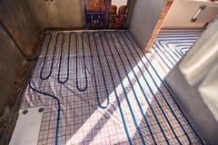 Τοποθέτηση των μπλε σωλήνων για τη θέρμανση πατωμάτων στο εργοτάξιο οικοδομής στοκ φωτογραφία