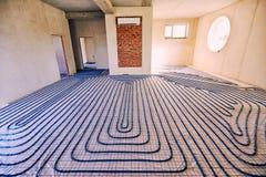 Τοποθέτηση των σωλήνων για τη θέρμανση πατωμάτων στο εργοτάξιο οικοδομής του χ στοκ φωτογραφίες