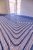 Τοποθέτηση των σωλήνων για τη θέρμανση πατωμάτων στο εργοτάξιο οικοδομής του χ στοκ εικόνες με δικαίωμα ελεύθερης χρήσης