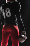 Τοποθέτηση φορέων αμερικανικού ποδοσφαίρου με τη σφαίρα στο μαύρο υπόβαθρο Στοκ Φωτογραφίες