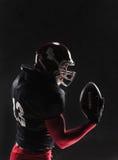 Τοποθέτηση φορέων αμερικανικού ποδοσφαίρου με τη σφαίρα στο μαύρο υπόβαθρο Στοκ εικόνες με δικαίωμα ελεύθερης χρήσης