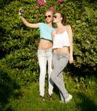 Τοποθέτηση δύο νέων κοριτσιών υπαίθρια Στοκ Εικόνες