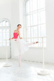 Τοποθέτηση Ballerina στα παπούτσια pointe στο άσπρο ξύλινο περίπτερο Στοκ Φωτογραφία