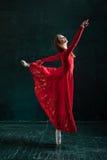 Τοποθέτηση Ballerina στα παπούτσια pointe στο μαύρο ξύλινο περίπτερο Στοκ Φωτογραφία