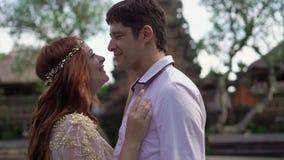 Τοποθέτηση Newlyweds κοντά στο βουδιστικό ναό στο Μπαλί Χέρια εκμετάλλευσης, αγκάλιασμα ρομαντικός γάμος φιλμ μικρού μήκους