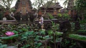 Τοποθέτηση Newlyweds κοντά στο βουδιστικό ναό στο Μπαλί Χέρια εκμετάλλευσης, αγκάλιασμα ρομαντικός γάμος απόθεμα βίντεο