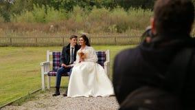 Τοποθέτηση Newlyweds στο φωτογράφο σε έναν πάγκο φιλμ μικρού μήκους