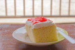 Τοποθετήστε το κέικ σε μια κρέμα και μια μαρμελάδα πιάτων, κόκκινες Στοκ φωτογραφία με δικαίωμα ελεύθερης χρήσης