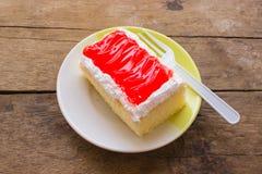 Τοποθετήστε το κέικ σε μια κόκκινη μαρμελάδα πιάτων Στοκ Εικόνες