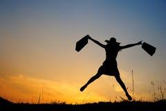 τοποθετεί την ευτυχή πηδώντας ψωνίζοντας sunse γυναίκα εκμετάλλευσης σε σάκκο Στοκ φωτογραφία με δικαίωμα ελεύθερης χρήσης
