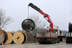 Τοποθετημένος ο φορτηγό γερανός ξεφορτώνει τα τύμπανα καλωδίων Στοκ Φωτογραφίες