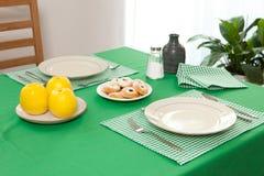 Τοποθετημένος πίνακας - δίκρανο και κουτάλι που τοποθετούνται στο πράσινο ύφασμα και το άσπρο πιάτο Στοκ Εικόνες