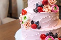 Τοποθετημένο στη σειρά ρόδινο γαμήλιο τρία κέικ που διακοσμείται με τα μούρα και τα λουλούδια Έννοια patisserie floristic από τη  Στοκ Φωτογραφία