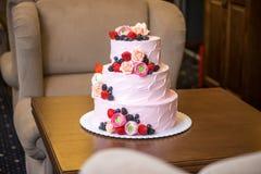 Τοποθετημένο στη σειρά ρόδινο γαμήλιο τρία κέικ που διακοσμείται με τα μούρα και τα λουλούδια Έννοια patisserie floristic από τη  Στοκ Εικόνες