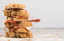 Τοποθετημένο στη σειρά σάντουιτς που γίνεται με με το ψωμί και το ζαμπόν σίκαλης Στοκ Εικόνα