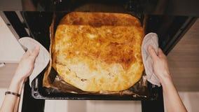 Τοπ άποψης ο θηλυκός φούρνος κουζινών χεριών ανοικτός με τους κατόχους δοχείων, παίρνει έξω ένα τηγάνι ψησίματος με την όμορφη πί απόθεμα βίντεο