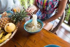 Τοπ άποψη γωνίας της γυναίκας που τρώει Chopstick νουντλς τους Unrecognizable ανθρώπους που δοκιμάζουν τα παραδοσιακά ασιατικά τρ Στοκ εικόνα με δικαίωμα ελεύθερης χρήσης