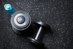 Τοπ άποψη δύο αλτήρων μετάλλων και ενός μπουκαλιού για το νερό, εξοπλισμός για την αθλητική ρουτίνα βάρους σε ένα θολωμένο υπόβαθ Στοκ εικόνα με δικαίωμα ελεύθερης χρήσης