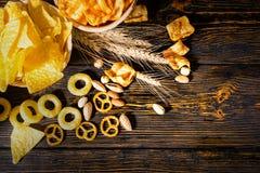 Τοπ άποψη δύο πιάτων με τα τσιπ κοντά στο σίτο, διεσπαρμένα καρύδια και Στοκ φωτογραφία με δικαίωμα ελεύθερης χρήσης