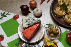 Τοπ άποψη δύο τύπων τυριών και ελιών στο υπόβαθρο των ζυμαρικών, του κρεμμυδιού, του σκόρδου και του πιπεριού σε μια πετσέτα στοκ εικόνα