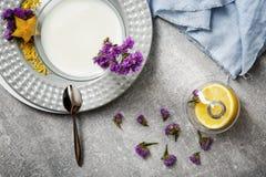 Τοπ άποψη ενός άσπρου καταφερτζή και χαριτωμένων λουλουδιών Ένα πιάτο με ένα κρύο ποτό σε ένα γκρίζο υπόβαθρο Κοκτέιλ και ένα λεμ Στοκ Εικόνα