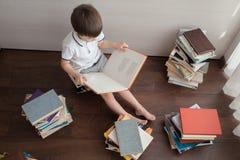 Τοπ άποψη ενός αγοριού και των βιβλίων στοκ εικόνες
