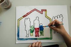 Τοπ άποψη ενός αγοριού που χρωματίζει μια εικόνα μιας οικογένειας σε ένα σπίτι στοκ εικόνες με δικαίωμα ελεύθερης χρήσης