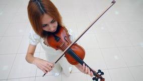 Τοπ άποψη ενός βιολιού που παίζεται κοντά από έναν θηλυκό μουσικό φιλμ μικρού μήκους