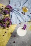 Τοπ άποψη ενός γυαλιού του καταφερτζή βανίλιας σε ένα ζωηρόχρωμο υπόβαθρο Μπλε και κίτρινο ύφασμα με τα πορφυρά λουλούδια ένα λευ Στοκ εικόνα με δικαίωμα ελεύθερης χρήσης