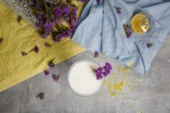 Τοπ άποψη ενός γυαλιού του καταφερτζή βανίλιας σε ένα ζωηρόχρωμο υπόβαθρο Μπλε και κίτρινο ύφασμα με τα πορφυρά λουλούδια ένα λευ Στοκ εικόνες με δικαίωμα ελεύθερης χρήσης