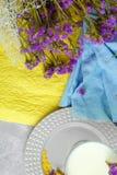 Τοπ άποψη ενός γυαλιού του καταφερτζή βανίλιας σε ένα ζωηρόχρωμο υπόβαθρο Μπλε και κίτρινο ύφασμα με τα πορφυρά λουλούδια ένα λευ Στοκ Φωτογραφίες