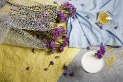 Τοπ άποψη ενός γυαλιού του καταφερτζή βανίλιας σε ένα ζωηρόχρωμο υπόβαθρο Μπλε και κίτρινο ύφασμα με τα ιώδη λουλούδια ένα λευκό Στοκ Φωτογραφίες